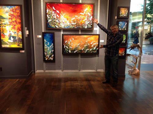 Gagnon devant ses peinture à la galerie d'art andrée laroche de